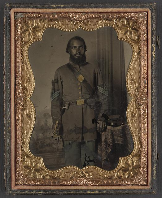 African American soldier in Union infantry sergeant's uniform and black mourning ribbon with bayonet in front of painted backdrop. Library of Congress Prints and Photographs Division Washington, D.C. 20540 USA.