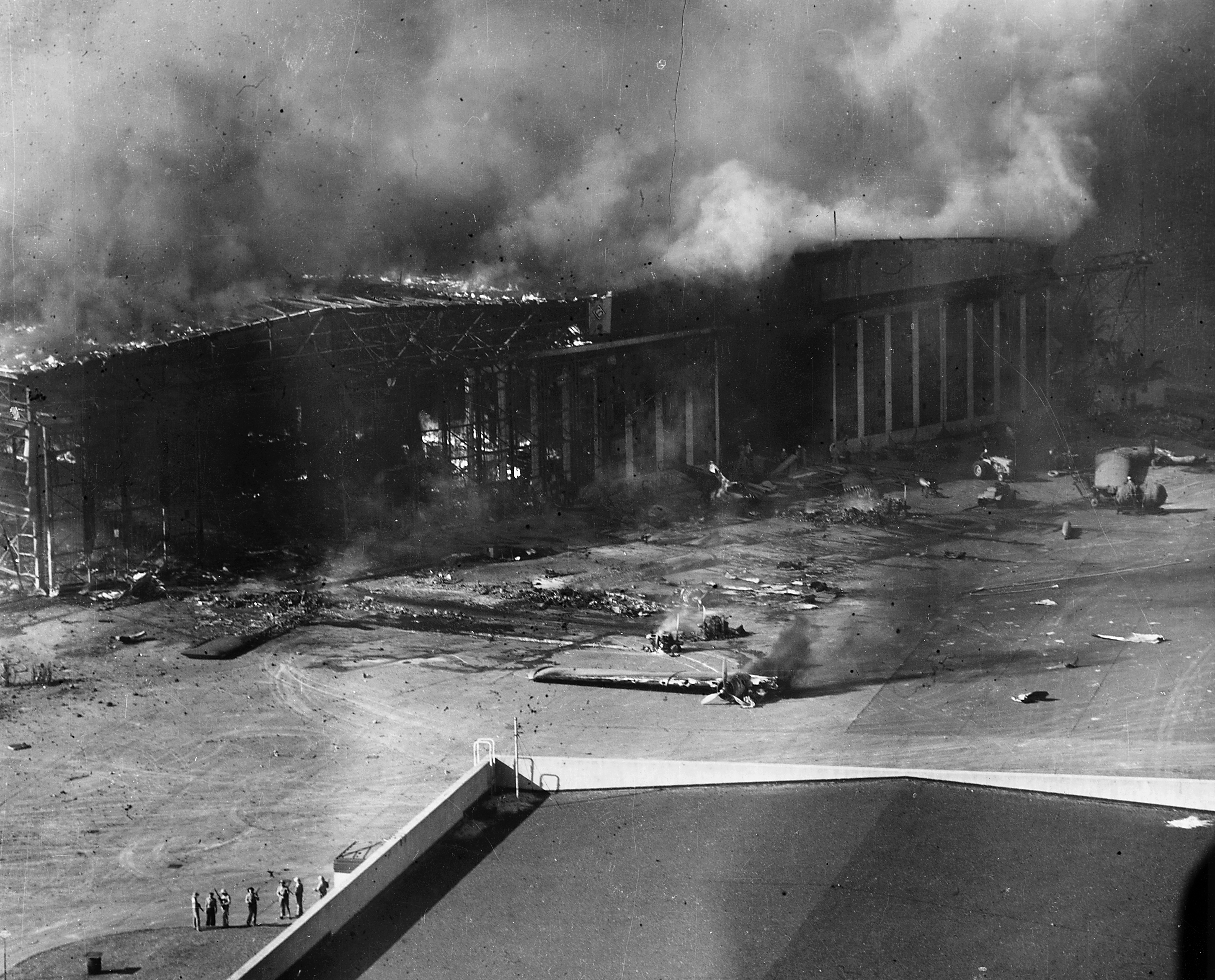 U.S. Navy planes and a hangar burning at the Ford Island Naval Air Station's seaplane base, during or immediately after the Japanese air raid on Pearl Harbor, Hawaii (USA), on 7 December 1941. The ruined wings of a Consolidated PBY Catalina patrol plane are at left and in the center. Note men with rifles standing in the lower left.