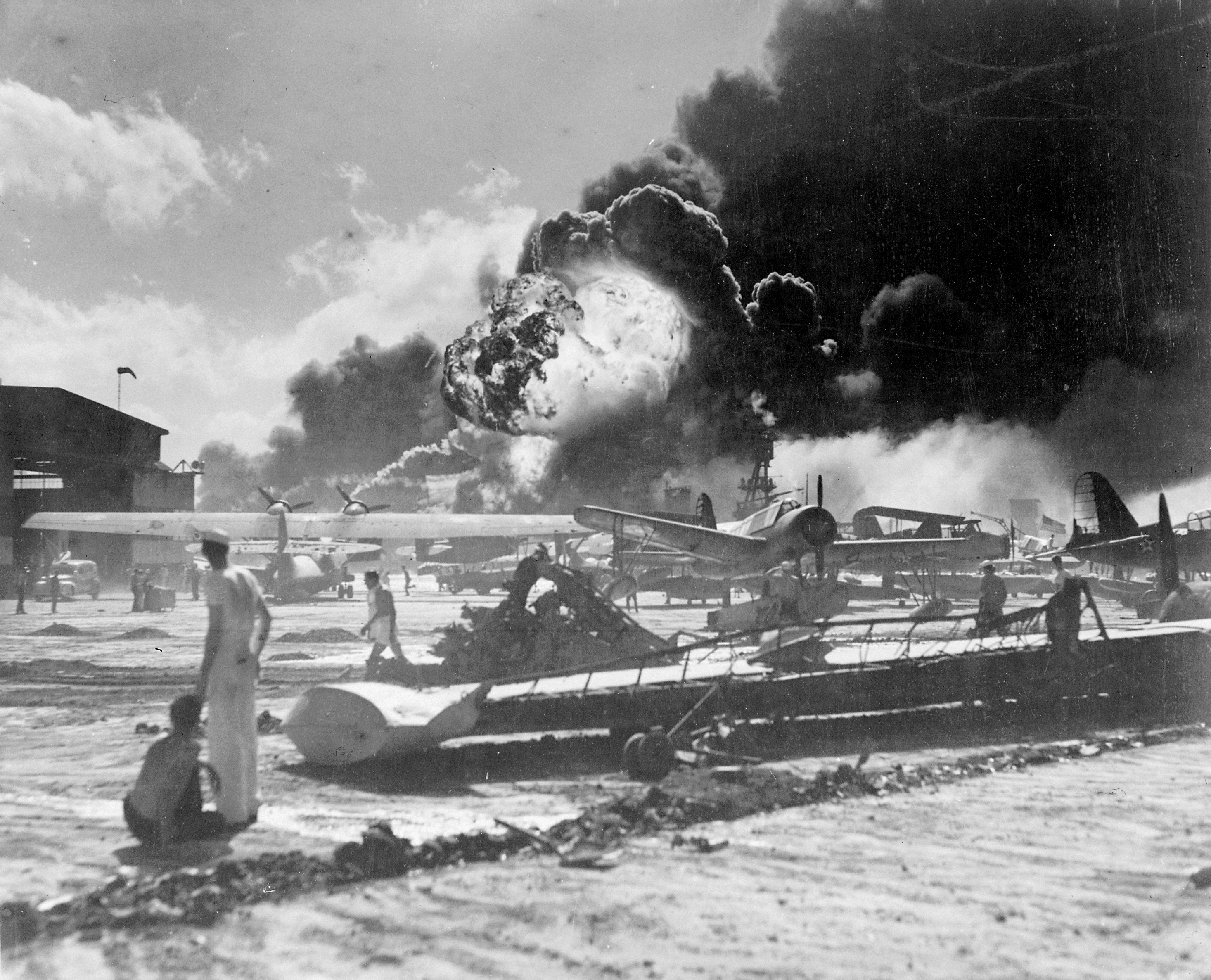 Sailors stand amid wrecked planes at the Ford Island seaplane base, watching as USS Shaw (DD-373) explodes in the center background, 7 December 1941. USS Nevada (BB-36) is also visible in the middle background, with her bow headed toward the left. Several planes are in the foreground, a consolidated PBY, Vought OS2Us and Curtiss SOCs. The wrecked wing in the foreground is from a PBY. Official U.S. Navy photograph 80-G-19948, now in the collections of the National Archives.