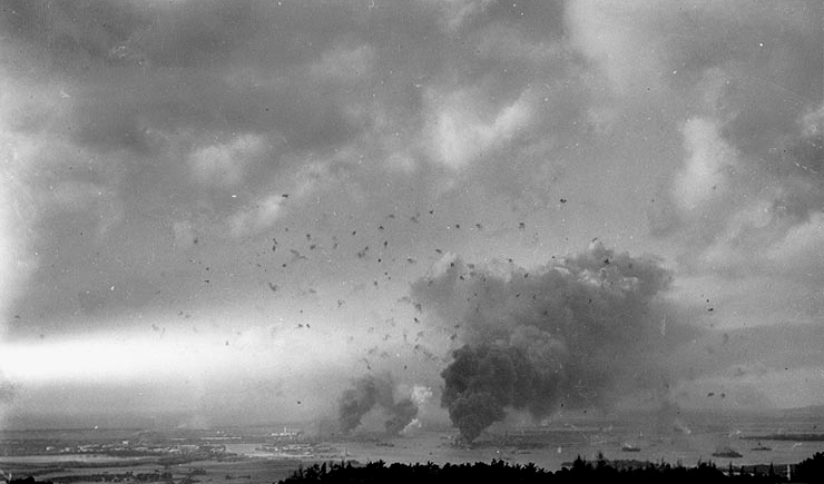 Panorama view of Pearl Harbor, during the Japanese raid on 7 December 1941, with anti-aircraft shell bursts overhead. The photograph looks southwesterly from the hills behind the harbor. Large column of smoke in lower right center is from the burning USS Arizona (BB-39). Smoke somewhat further to the left is from the destroyers Shaw (DD-373), Cassin (DD-372) and Downes (DD-375), in drydocks at the Pearl Harbor Navy Yard. 7 December 1941. Official U.S. Navy photograph.