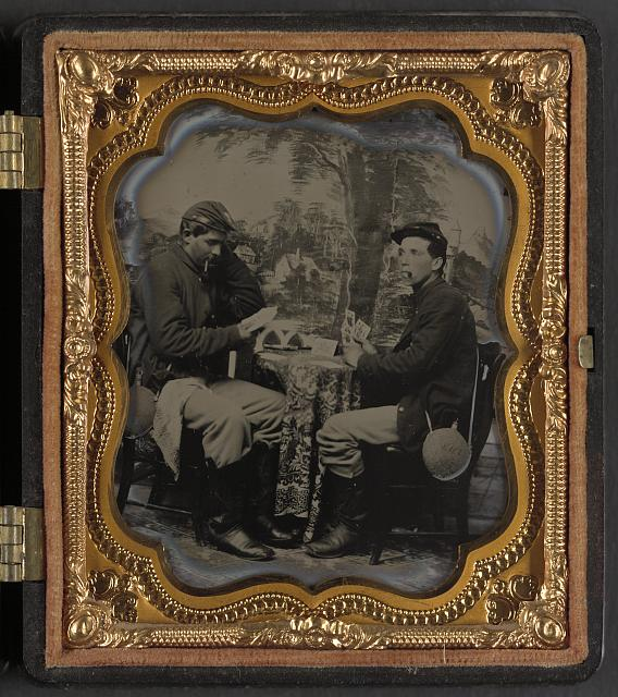 [Two unidentified soldiers in Union uniforms with canteens playing cards and smoking in front of painted backdrop showing landscape with houses and trees]