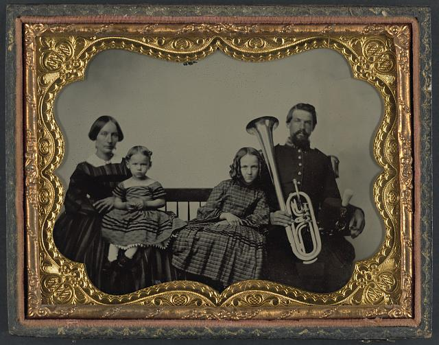 Unidentified soldier in Union uniform with wife and daughters holding saxhorn between 1861 and 1865. Library of Congress Prints and Photographs Division Washington, D.C. 20540.
