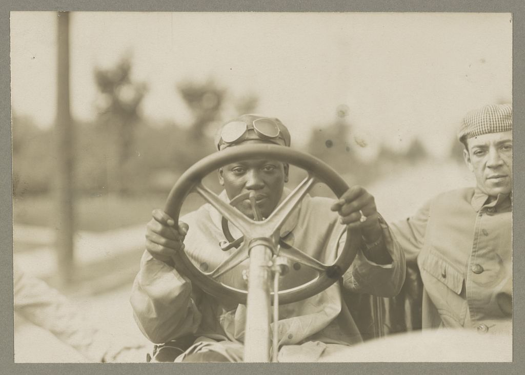 Photograph shows Jack Johnson looking through the steering wheel of his Thomas Flyer automobile, with another man seated next to him. September 6, 1910.